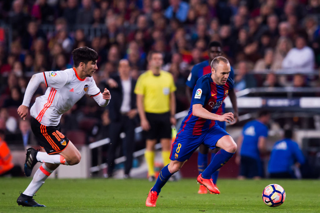 Andres Iniesta of FC Barcelona conducts the ball past Carlos Soler